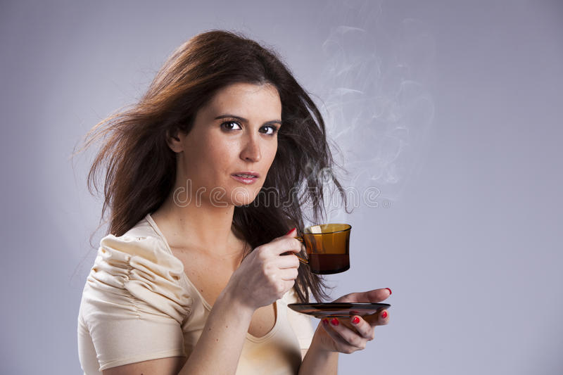 Woman drinking a hot drink. Beautiful woman portrait holding a mug with some hot drink royalty free stock photo