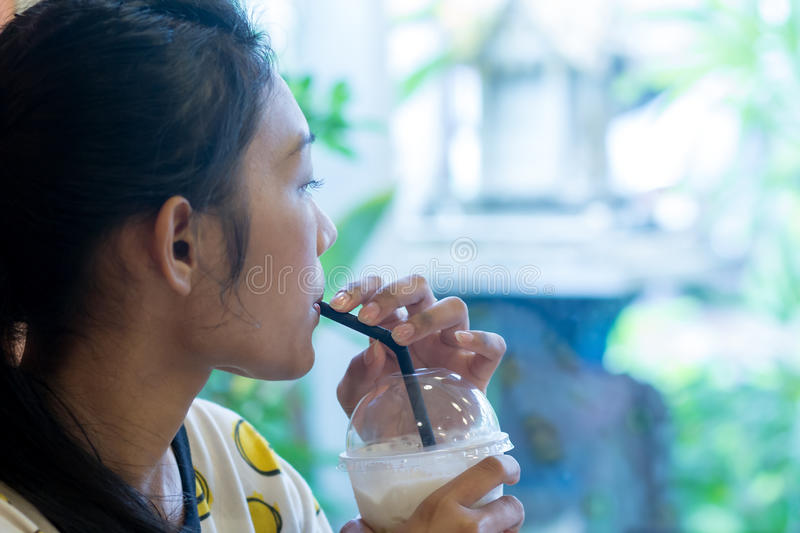 Woman drinking iced coffee. From a plastic cup with a straw stock images