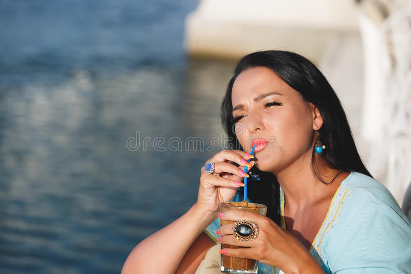 Woman drinking iced coffee in seaside cafe. Happy tanned woman drinking iced coffee in seaside cafe during sunset. Selective focus, copy space stock photos