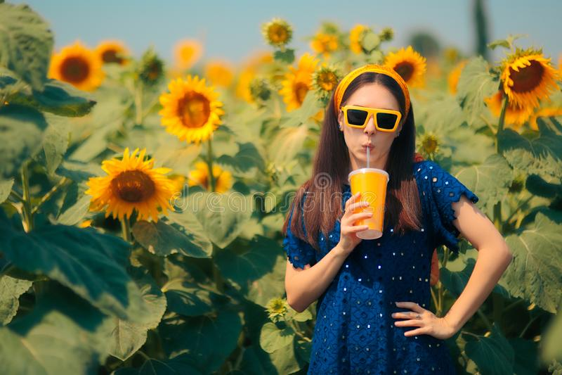Woman Drinking Juice in Summer Sunflower Field stock photos