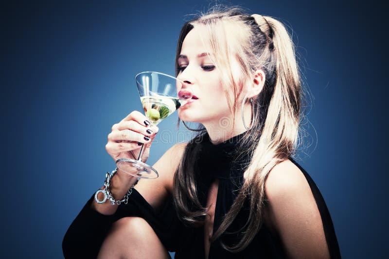 Woman drinking martini. Blond woman drinking martini, studio shot royalty free stock photo