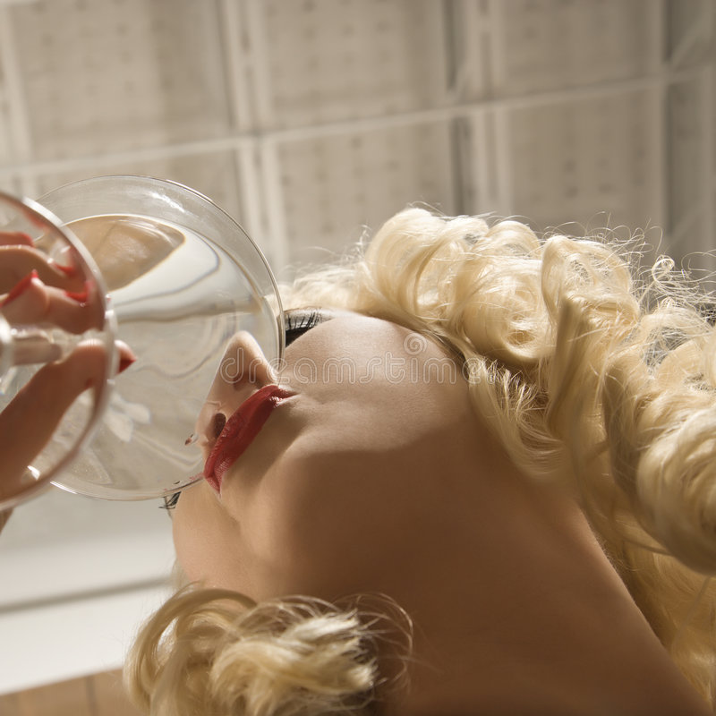 Woman drinking martini royalty free stock image