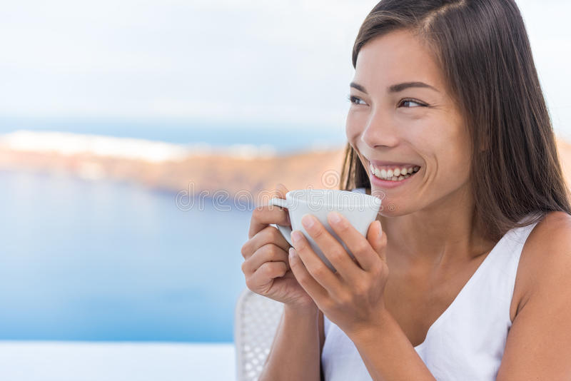 Woman Drinking Morning Coffee At Breakfast. Beautiful young lady having coffee on terrace by sea at resort. Woman is on her vacation in Santorini, Greece royalty free stock photo