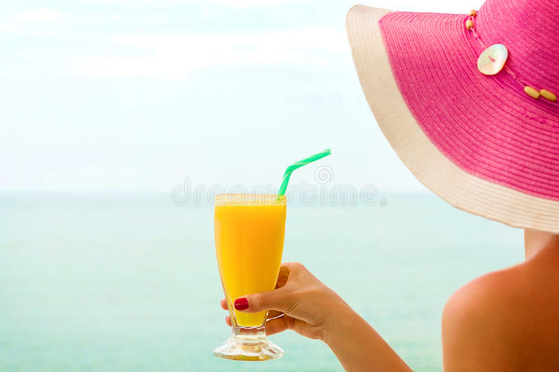 Woman drinking orange juice, on the beach. Young female, drinking orange juice, on the beach royalty free stock image