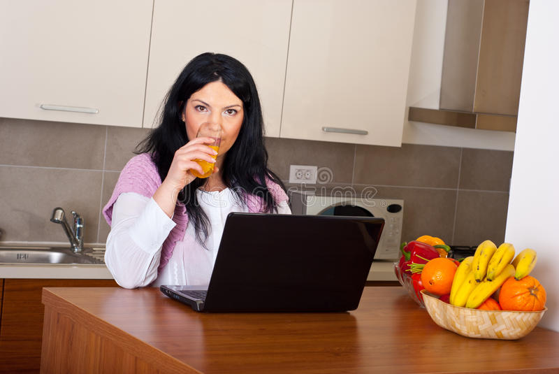 Woman Drinking Orange Juice In Kitchen Royalty Free Stock Image