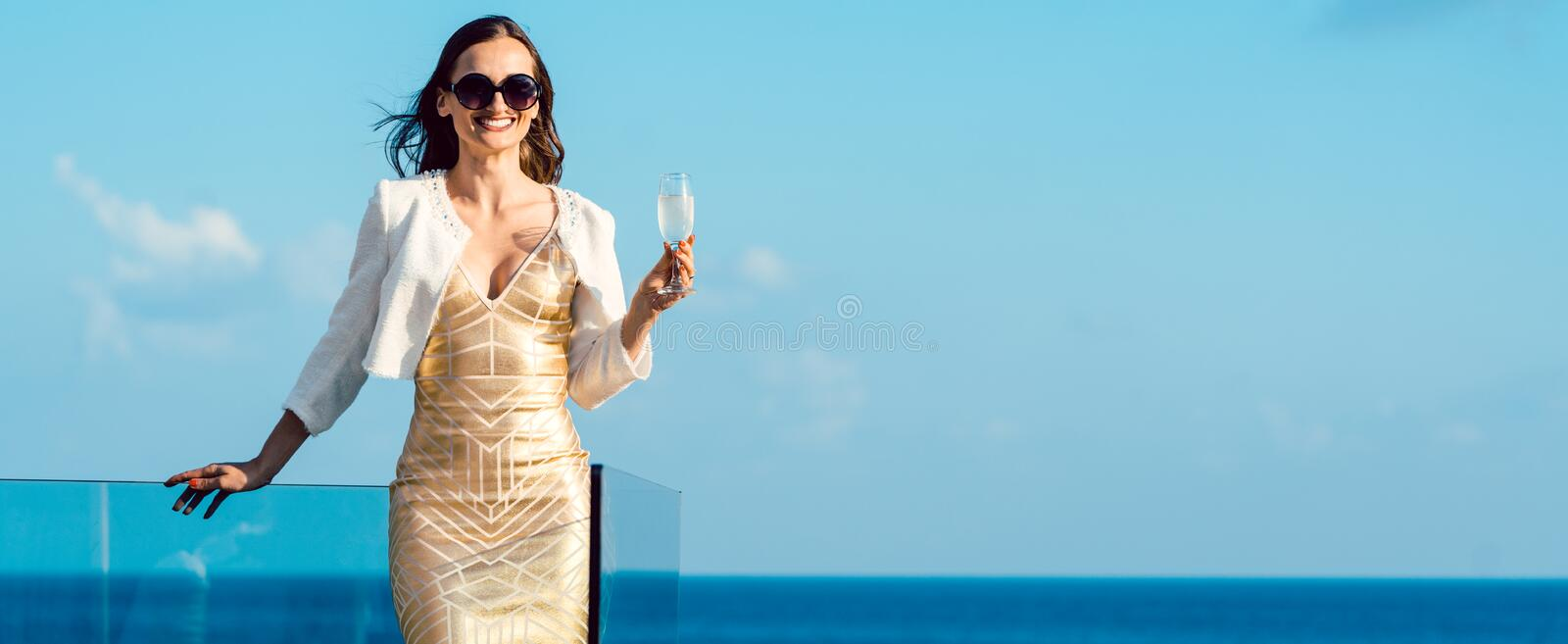 Woman drinking sparkling wine looking over ocean royalty free stock images