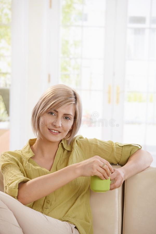 Woman drinking tea on couch at home. Portrait of young blonde woman sitting on couch at home, drinking tea, looking at camera smiling stock images