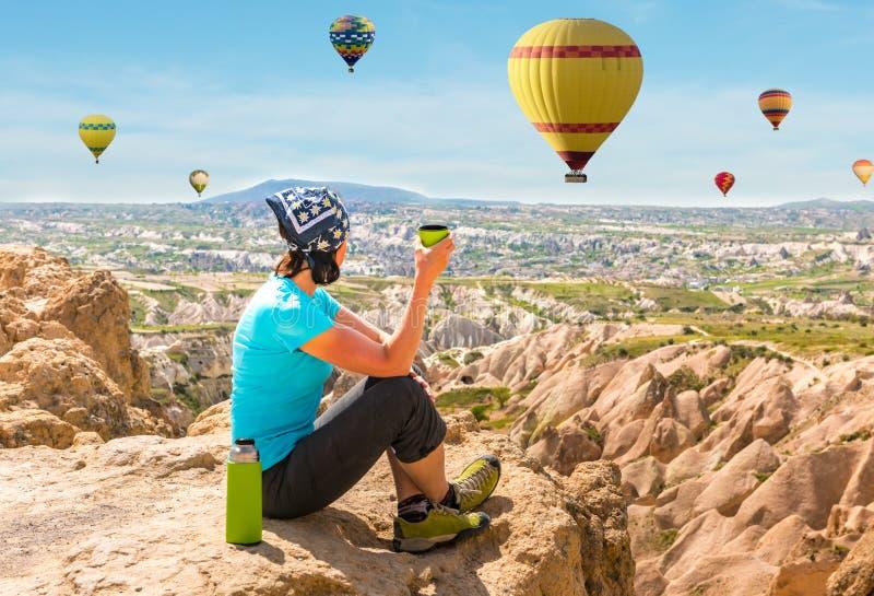 Woman drinking tea and looking at hot air balloons, Cappadocia stock photo