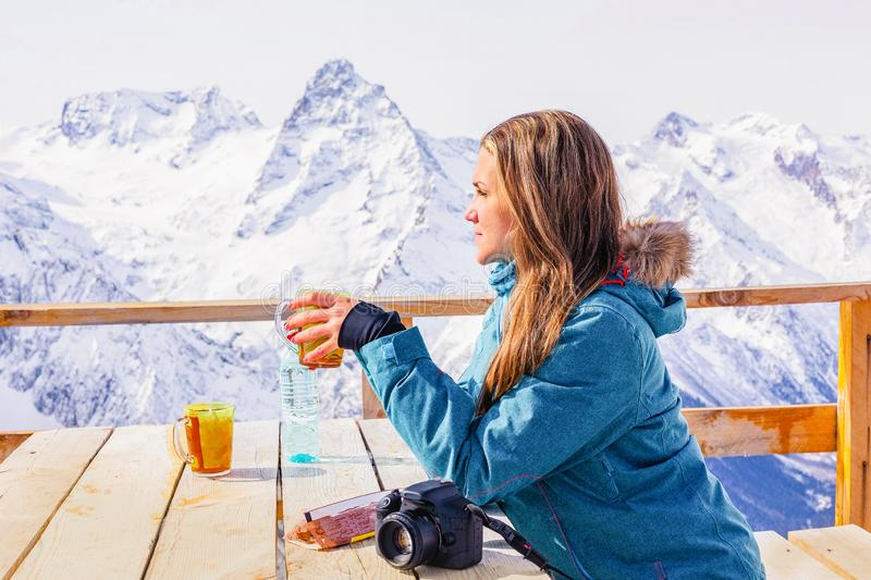 Woman drinking tea in the rustic wooden outdoor cafe mountain summit. Lifestyle adventure concept. Alpine view with snow peaks. stock photo