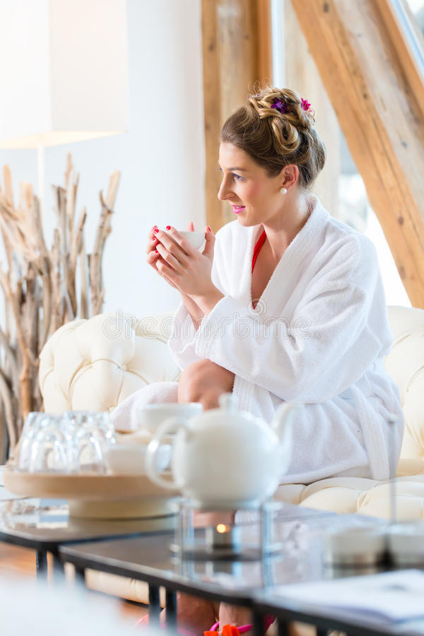 Woman drinking tea in wellness spa. Woman in bath robe drinking tea in wellness spa relaxation room stock images
