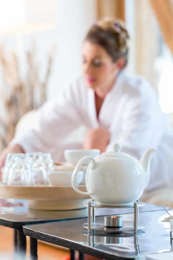 Woman drinking tea in wellness spa. Woman in bath robe drinking tea in wellness spa relaxation room royalty free stock photography