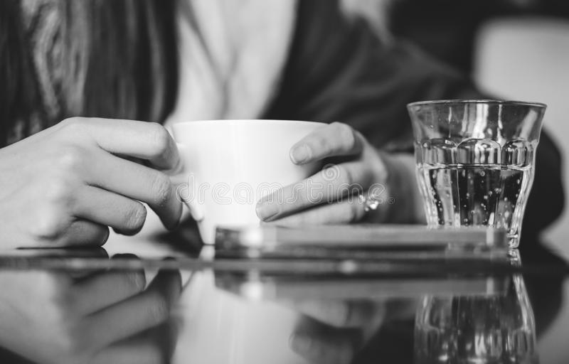 Woman drinking a warm coffee in a bar - Female hands holding a cup of hot beverage with a glass of sparkling water stock photography