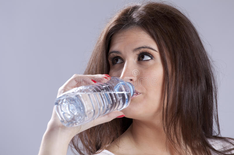 Woman drinking water. Beautiful young woman drinking water from plastic bottle stock photo