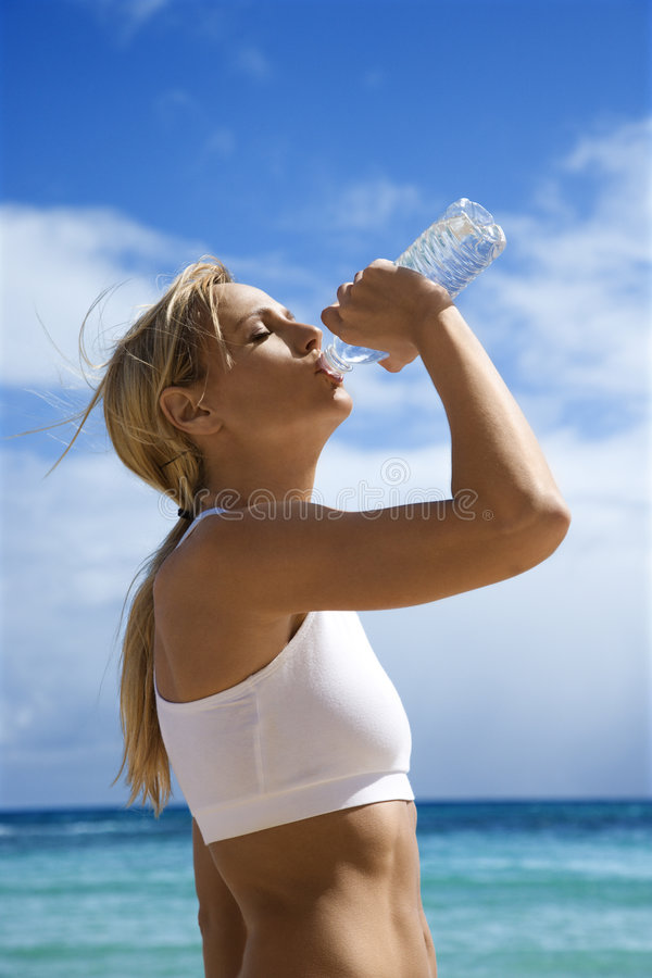 Woman drinking water on beach. stock images