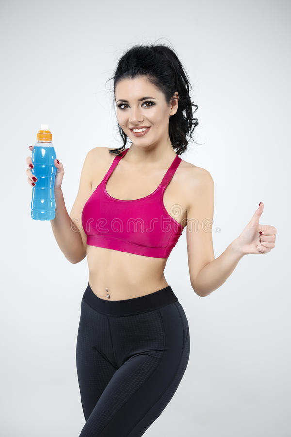 Woman drinking water from bottle after exercise. Attractive woman drinking water from bottle after exercise stock photo