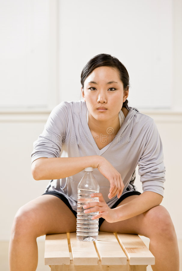 Woman drinking water from bottle in health club royalty free stock images