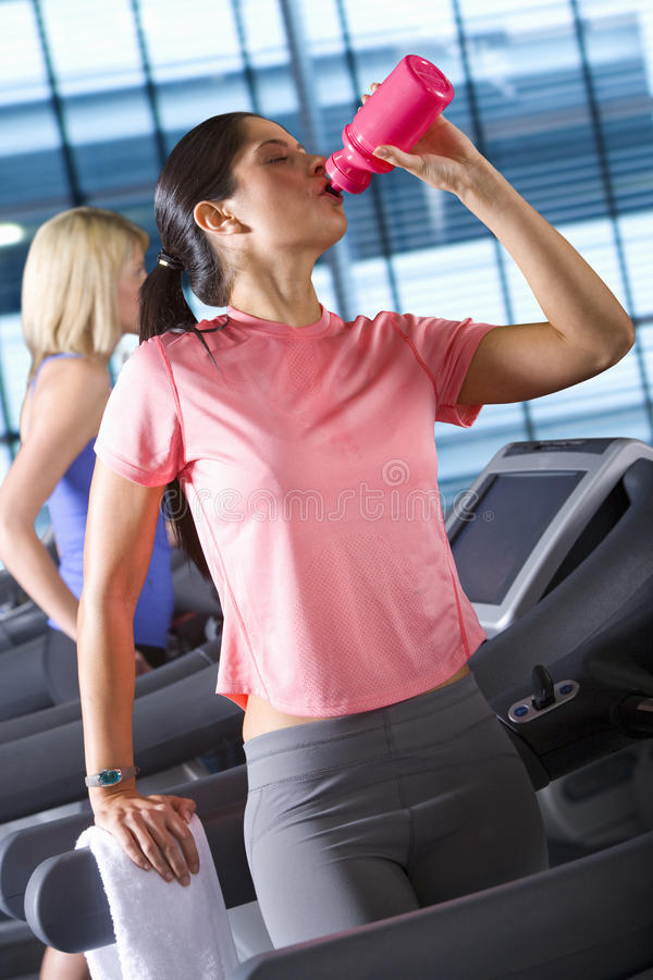 Woman drinking from water bottle on treadmill in health club stock images