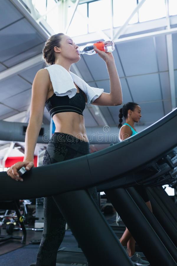 Woman drinking water while exercising on a treadmill in fitness center stock images