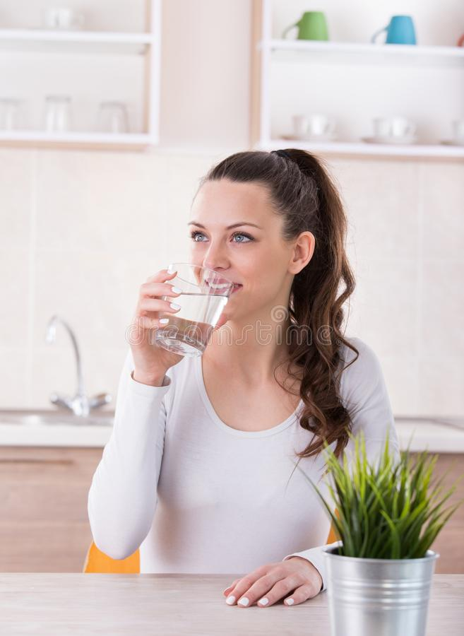 Woman drinking water in kitchen stock photo