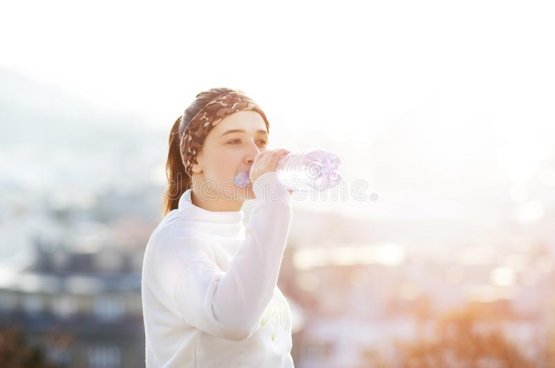 Woman drinking water during a running. Cold weather. Jogging woman in a city during a winter. Sunny day. Drinking mode. Woman drinking water during a running royalty free stock photo