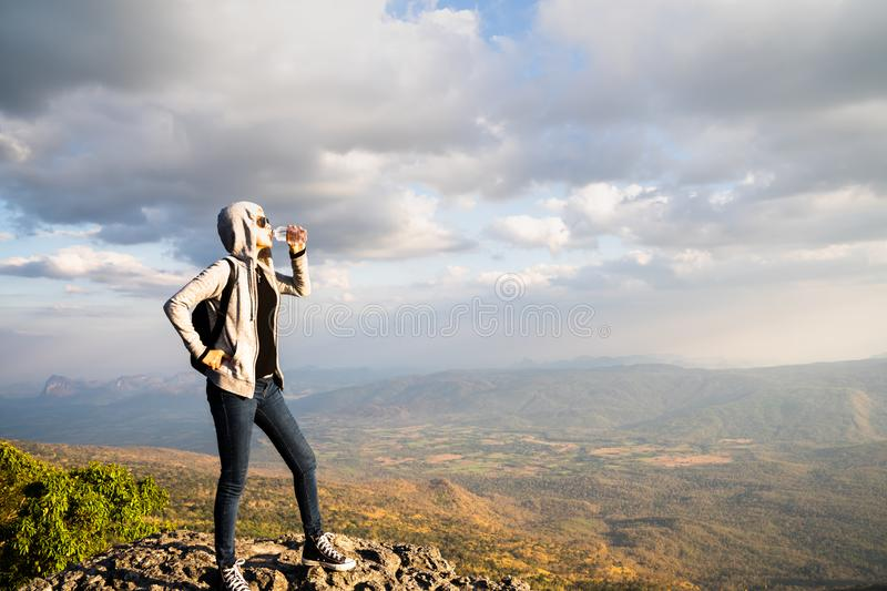 A woman drinking water and standing on rocky mountain looking out at scenic natural view and beautiful blue sky royalty free stock photos