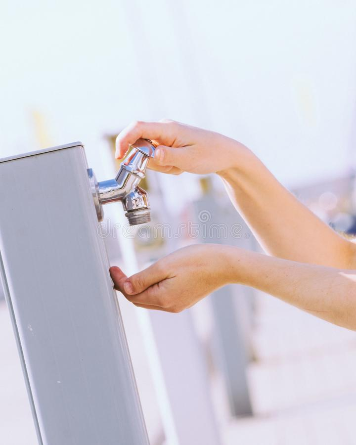 Woman drinking water from street tap royalty free stock photo