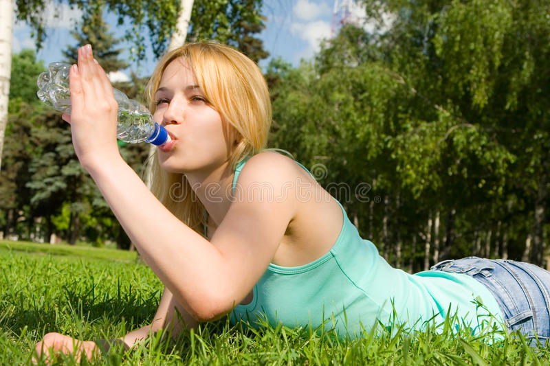 Woman drinking water on the summer glade. Pretty woman drinking water on the summer glade stock image