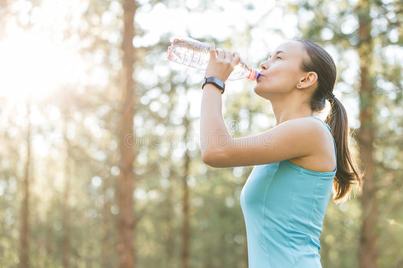 Woman drinking water after work out exercising on sunset evening royalty free stock images