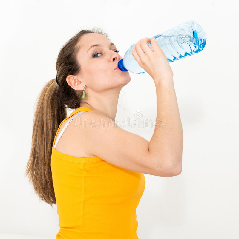 Woman drinking water. Young woman drinking water against white background royalty free stock photography