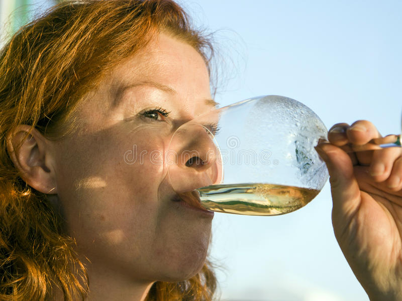 Woman drinking white wine royalty free stock images