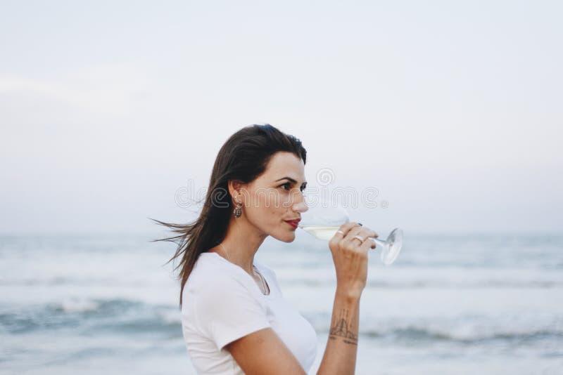 Woman drinking wine on beach royalty free stock image