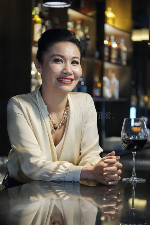 Woman drinking wine. Portrait of middle-aged Vetnamese woman resting in restaurant with glass on wine royalty free stock image