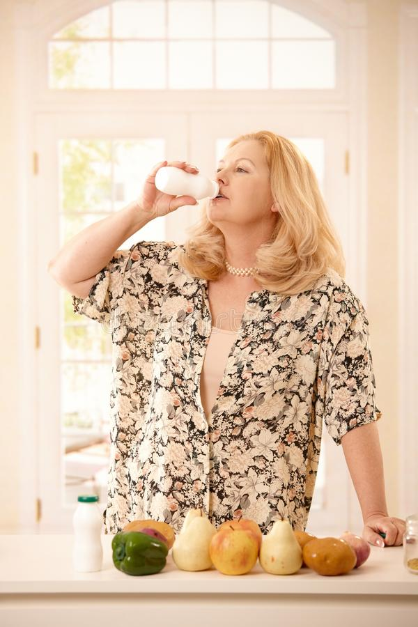 Woman drinking yogurt in kitchen