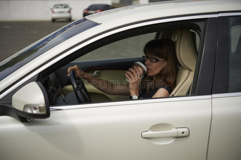 Woman drinks coffee in the car royalty free stock image