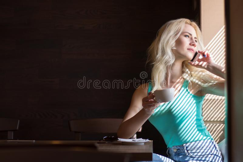 Woman Drinks Coffee and Looks out the Window with Blinds. stock photos