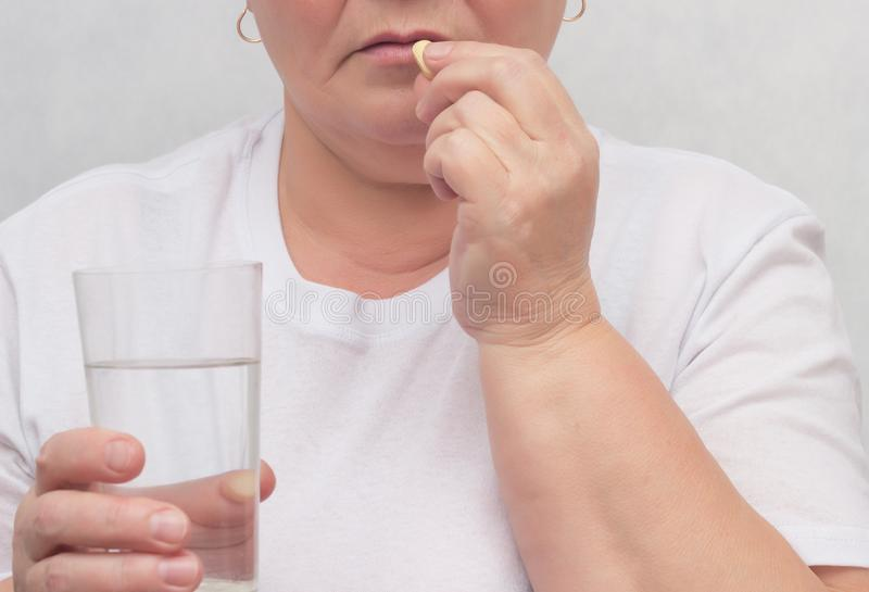 A woman drinks a hormonal pill for treating the thyroid gland, eliminating nodules and normalizing hormones, treatment, close-up royalty free stock photos