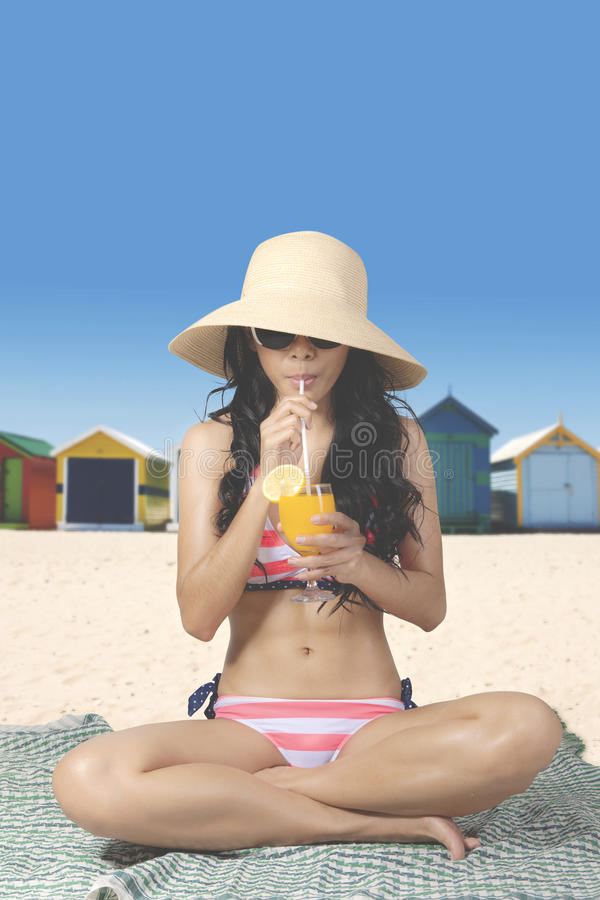 Woman drinks orange juice on beach. Summer Concept. Young woman drinks a glass of fresh orange juice while sitting on the beach and wearing a striped bikini with stock photography