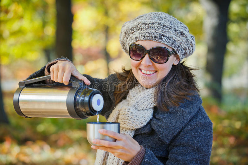 Woman drinks tea in autumn park