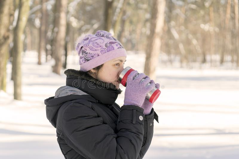 woman drinks tea out of cup. Winter forest. Young man in a red warm jacket with knitted hat and scarf standing on snowy background stock image