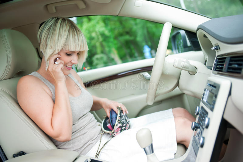 Woman driver. Woman sitting in drivers seat of her luxury car talking to mobile phone and searching purse royalty free stock photography