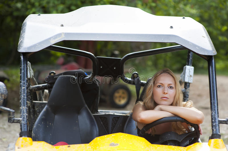 Woman driver behind the wheel of buggy. Young beautiful woman driver behind the wheel of the buggy at tropical jungle stock image
