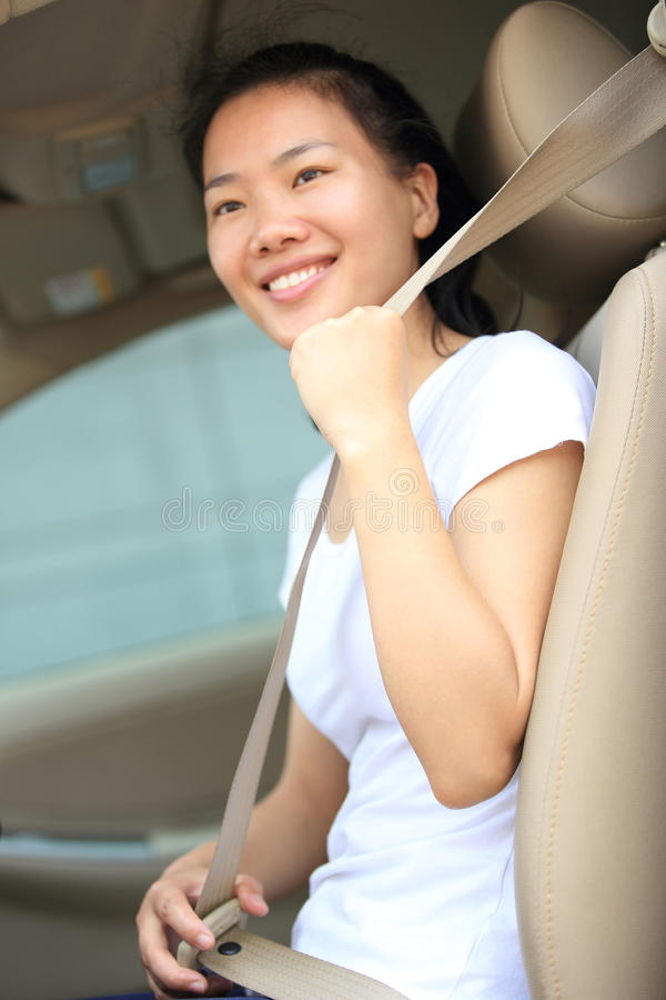 Woman driver buckle up the seat belt in car stock image