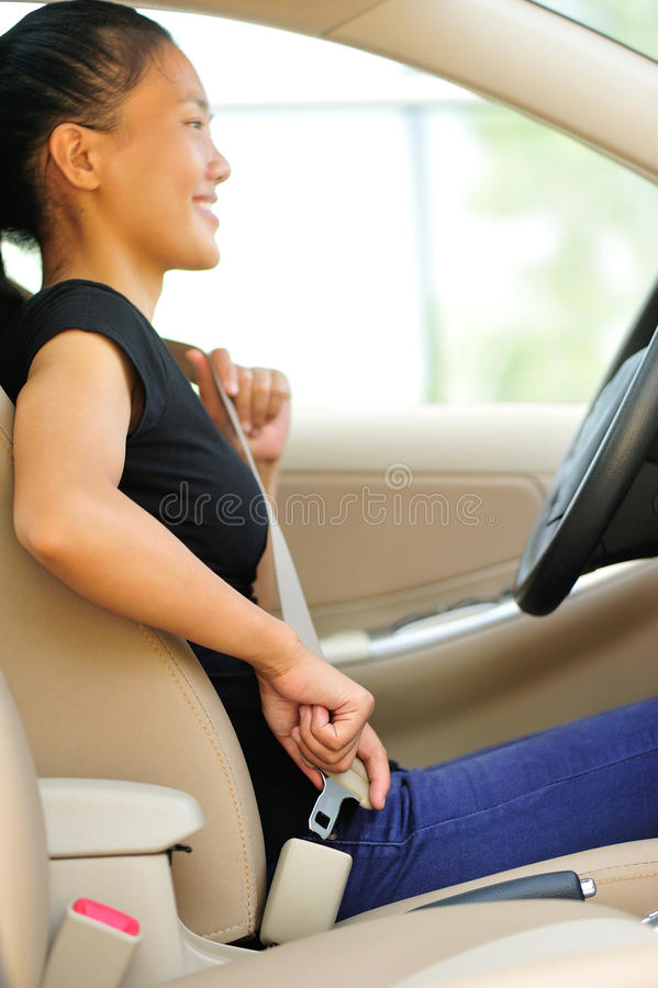 Woman driver buckle up the seat belt in car royalty free stock images