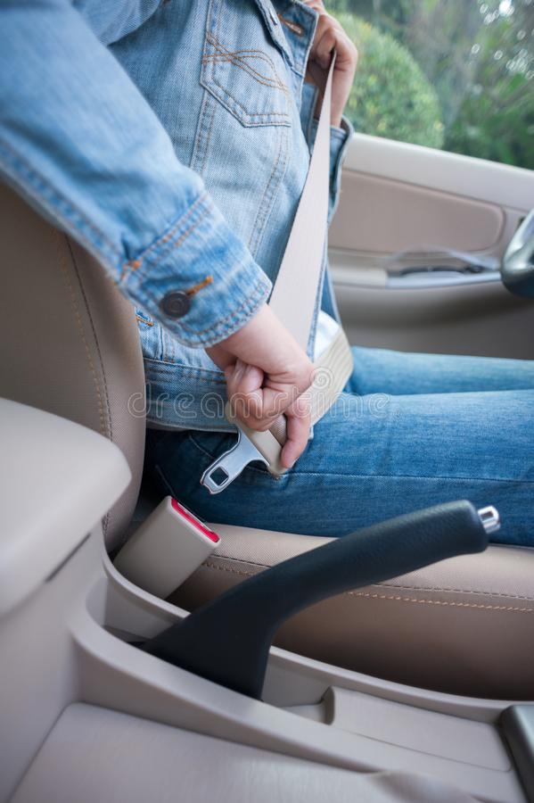 Woman driver buckle up the seat belt stock photography