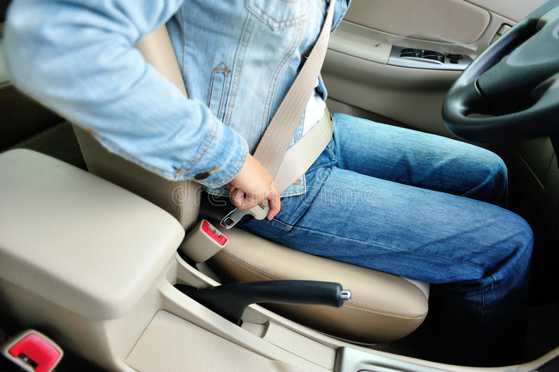 Woman driver buckle up the seat belt royalty free stock images