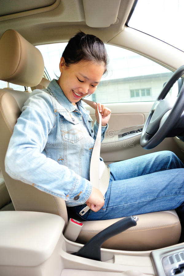 Woman driver buckle up the seat belt royalty free stock image