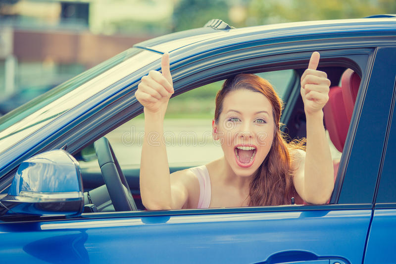 Woman driver happy smiling showing thumbs up sitting inside new car. Side door view woman driver happy smiling showing thumbs up sitting inside new blue car stock photography