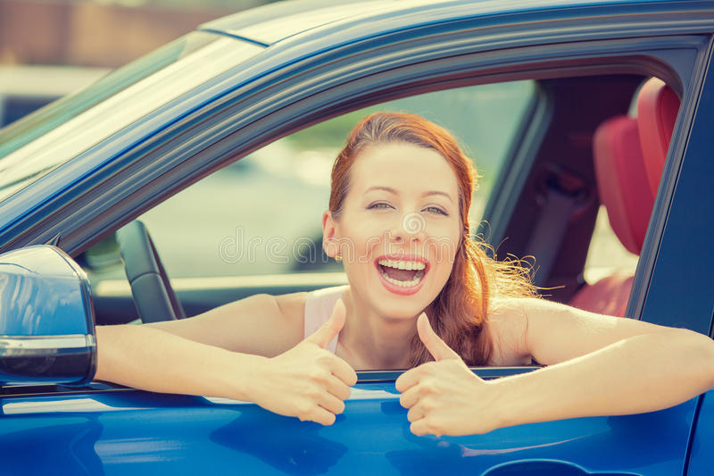 Woman driver happy smiling showing thumbs up sitting inside new car. Side door view woman driver happy smiling showing thumbs up sitting inside new blue car stock photos