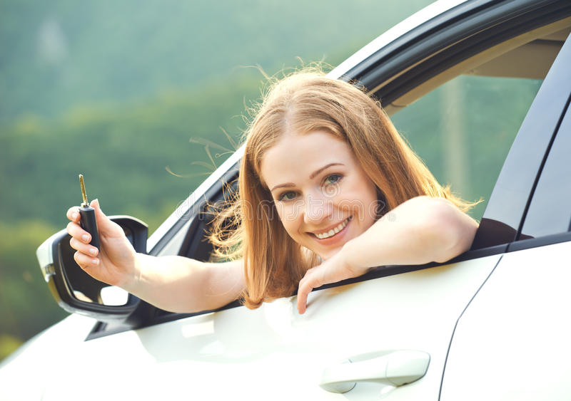 Woman driver with keys driving a new car. Happy woman driver with keys driving a new car royalty free stock photography