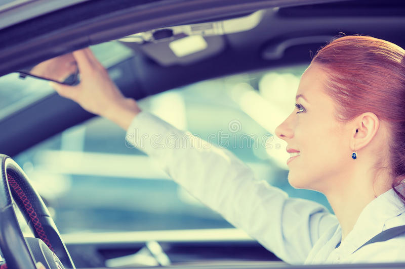Woman driver looking adjusting rear view car mirror. Happy young woman driver looking adjusting rear view car mirror, making sure line is free visibility is good royalty free stock photos